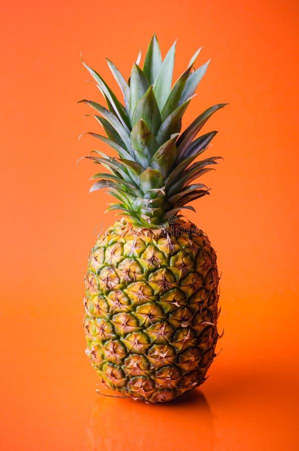 Pineapple on orange background, vertical shot. Picture presents pineapple on orange background, vertical shot royalty free stock image