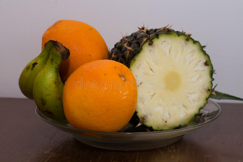 Pineapple, oranges and bananas on a plate on the table royalty free stock photo