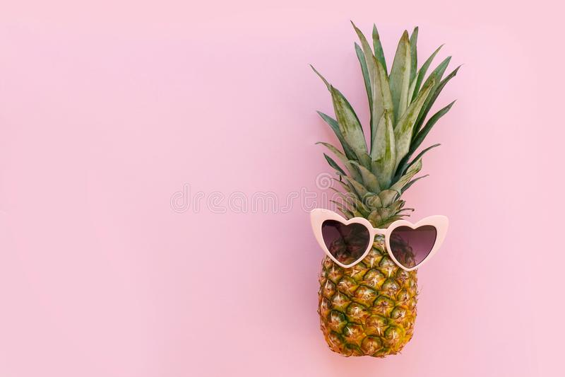Pineapple in pink sunglasses on trendy pink paper background. mi royalty free stock photos