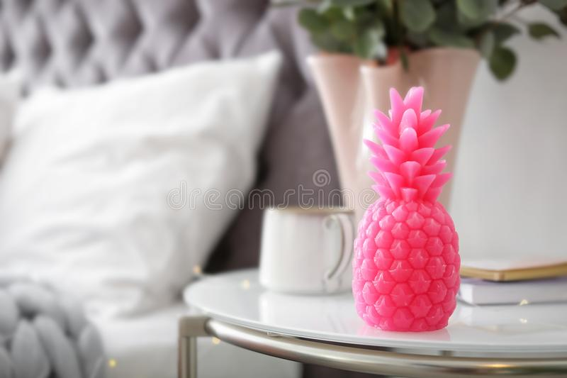 Pineapple shaped candle on bedside table. In room royalty free stock images