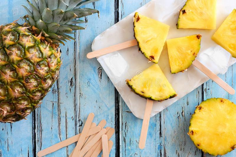 Pineapple slice popsicles, top view over blue wood stock image