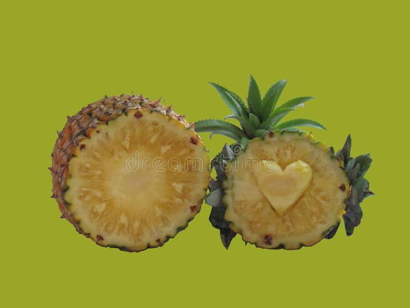 Pineapple sliced in half carved heart. And decorated with pineapple plants, Dwarf pineapple same plant species on green. Background. concept Fruit for health stock images