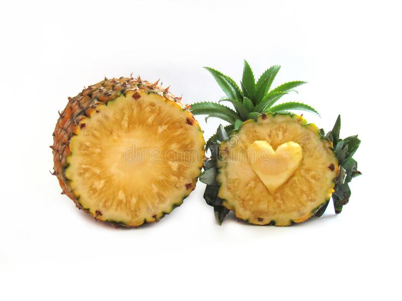 Pineapple sliced in half carved heart. And decorated with pineapple plants, Dwarf pineapple same plant species on a white. Background. concept Fruit for health stock photos