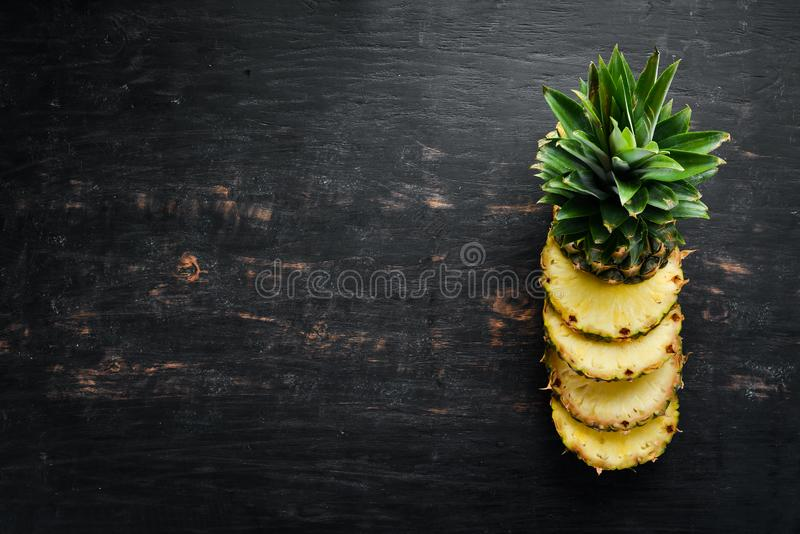 Pineapple. Sliced pineapple on a wooden background. stock photo