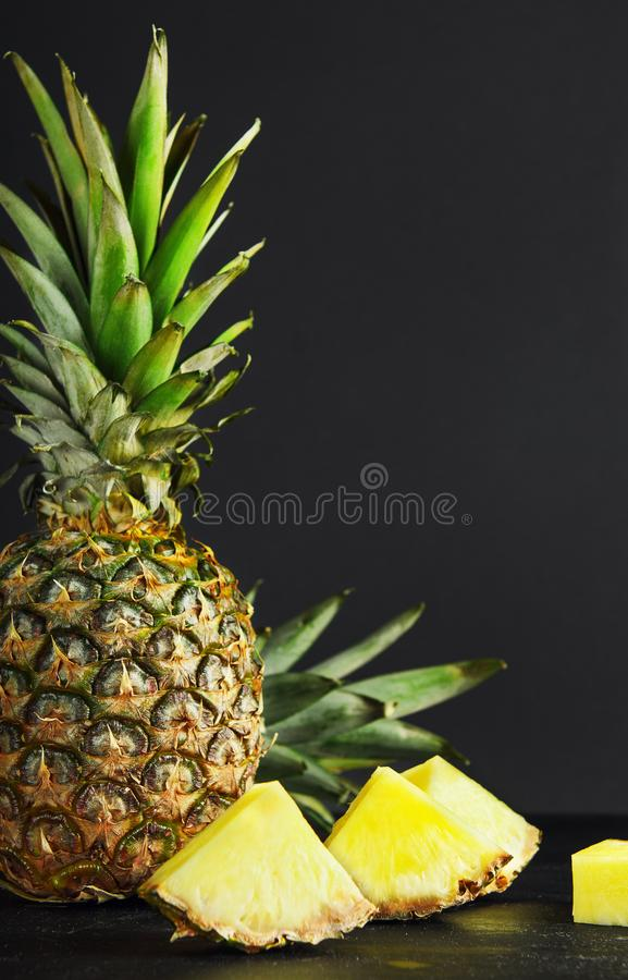 Pineapple and pineapple slices on black background. Delicious, juicy, dietary, summer fruit. Copy space. royalty free stock photography