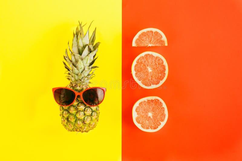 Pineapple sunglasses slices grapefruit colorful background Flat stock image