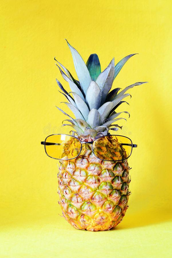 Pineapple with sunglasses yellow on a yellow background. Beach and tropical royalty free stock image