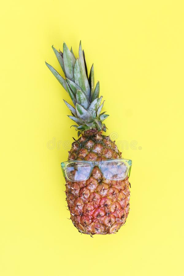 Pineapple with sunglasses in yellow background royalty free stock photo