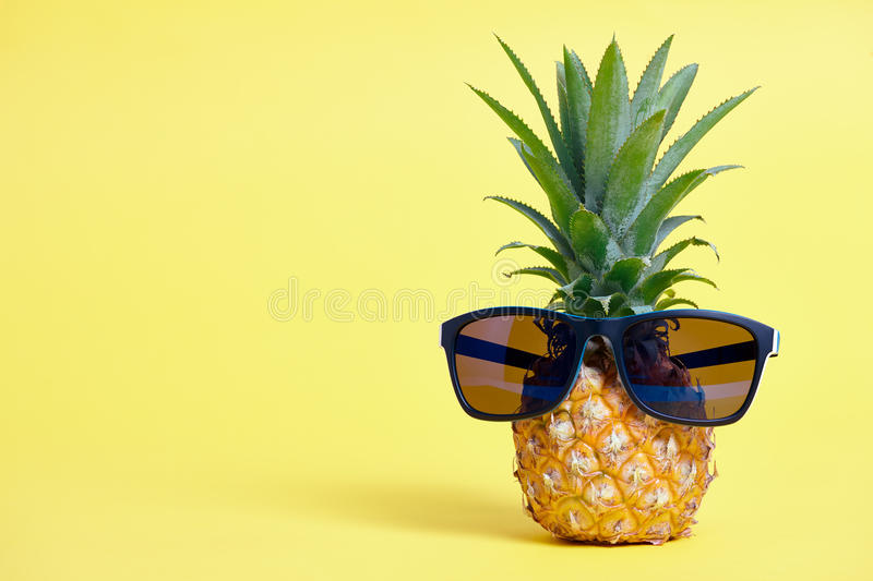Pineapple with sunglasses on yellow background stock photos