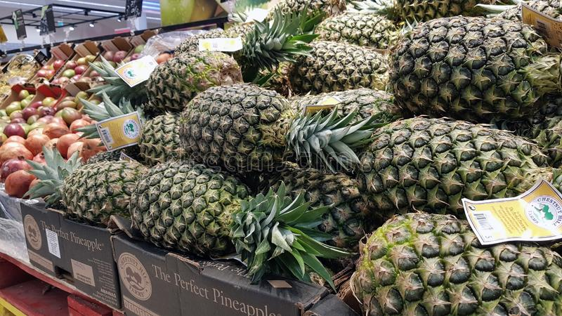 Pineapple in supermarket. PIATRA NEAMT, ROMANIA - MARCH 16: Fruits & x28;pineapple& x29; in supermarket aisle in Shopping Center on March 16, 2018 in Piatra royalty free stock photos
