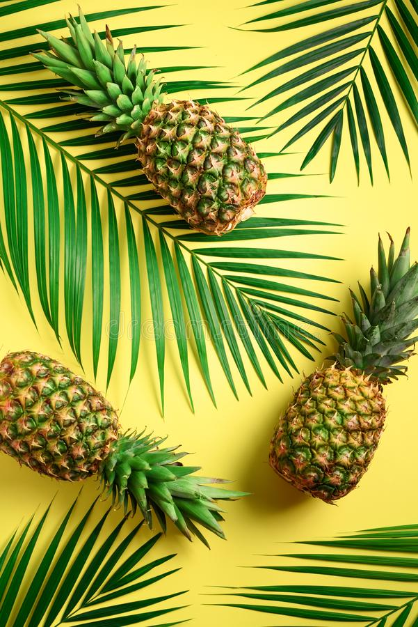 Pineapple and tropical palm leaves on yellow background. Top view. Summer concept. Creative flat lay with copy space. royalty free stock image