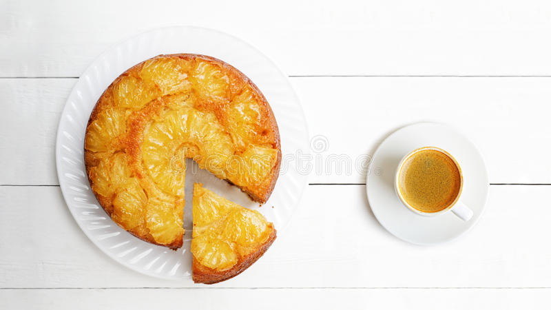 Pineapple Upside Down Cake and cup of coffee on white wooden tab stock photos