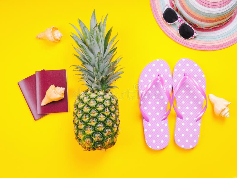 Pineapple wearing sunglasses on a yellow background. Summer flat lay: two passports, fresh pineapple wearing sunglasses, beach slippers and colorful hat on a royalty free stock image