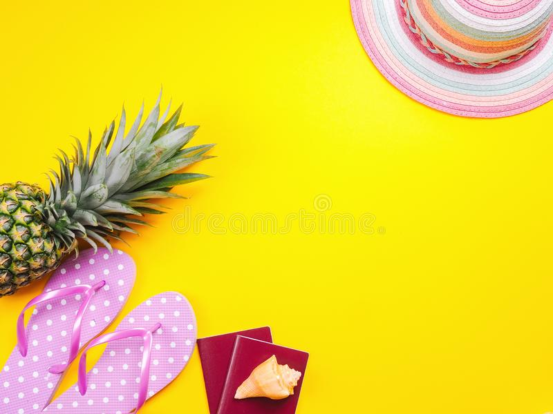 Pineapple wearing sunglasses on a yellow background. Summer flat lay: two passports, fresh pineapple wearing sunglasses, beach slippers and colorful hat on a royalty free stock photo