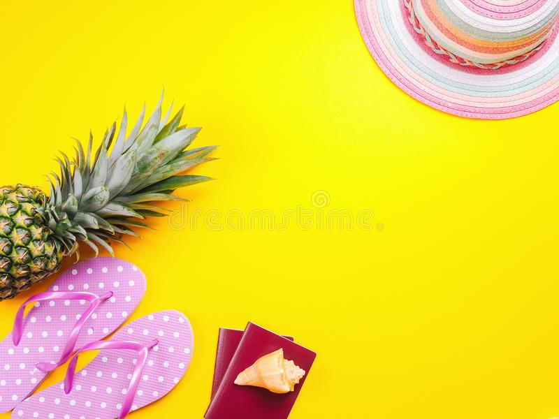 Pineapple wearing sunglasses on a yellow background. Summer flat lay: two passports, fresh pineapple wearing sunglasses, beach slippers and colorful hat on a stock images