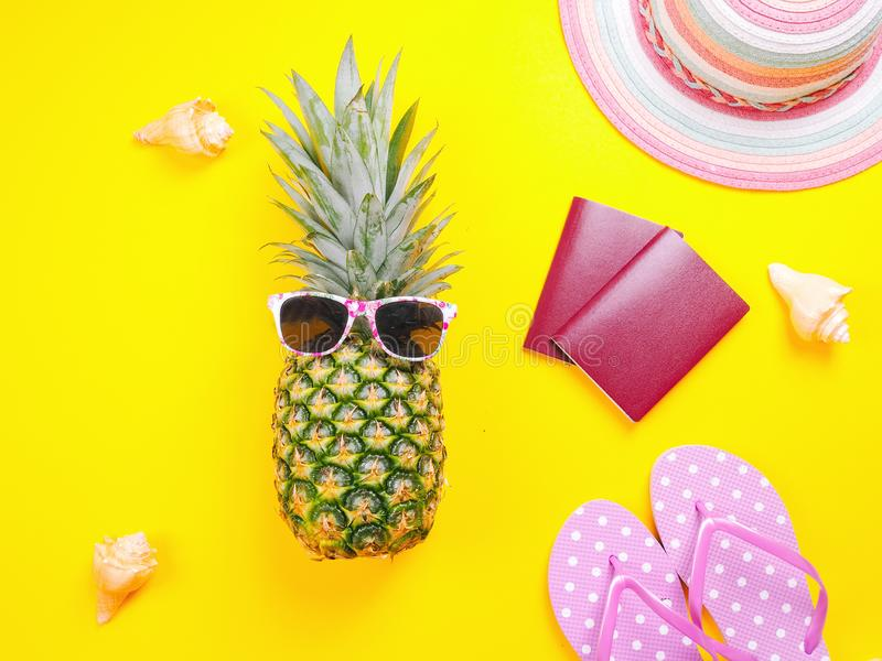 Pineapple wearing sunglasses on a yellow background. Summer flat lay: two passports, fresh pineapple wearing sunglasses, beach slippers and colorful hat on a royalty free stock photos