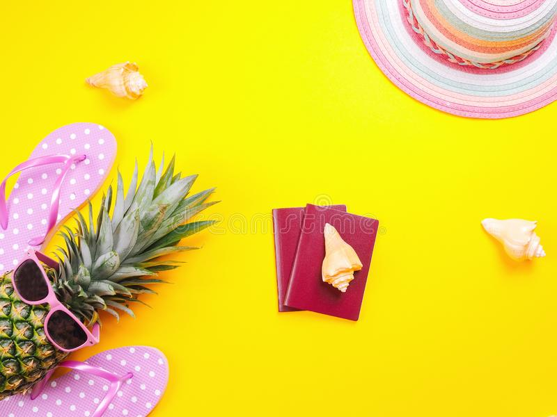Pineapple wearing sunglasses on a yellow background. Summer flat lay: two passports, fresh pineapple wearing sunglasses, beach slippers and colorful hat on a royalty free stock images