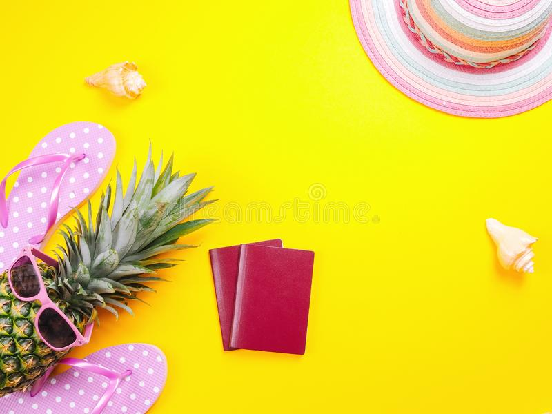 Pineapple wearing sunglasses on a yellow background. Summer flat lay: two passports, fresh pineapple wearing sunglasses, beach slippers and colorful hat on a stock photo
