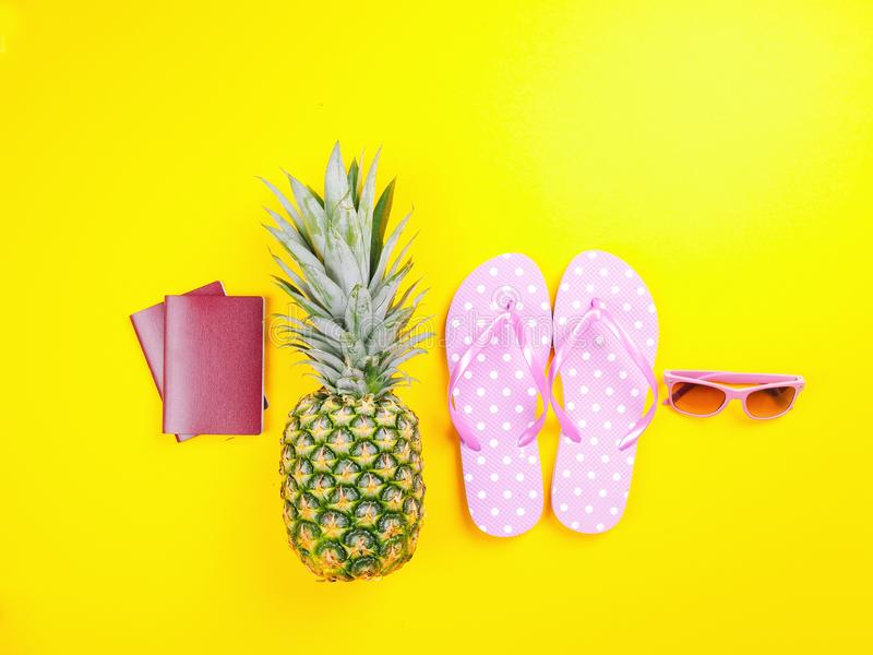 Pineapple wearing sunglasses on a yellow background. Summer flat lay: two passports, fresh pineapple wearing sunglasses, beach slippers and colorful hat on a stock photos