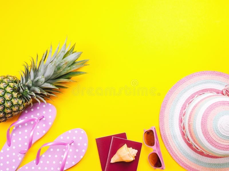 Pineapple wearing sunglasses on a yellow background. Summer flat lay: two passports, fresh pineapple wearing sunglasses, beach slippers and colorful hat on a royalty free stock photography