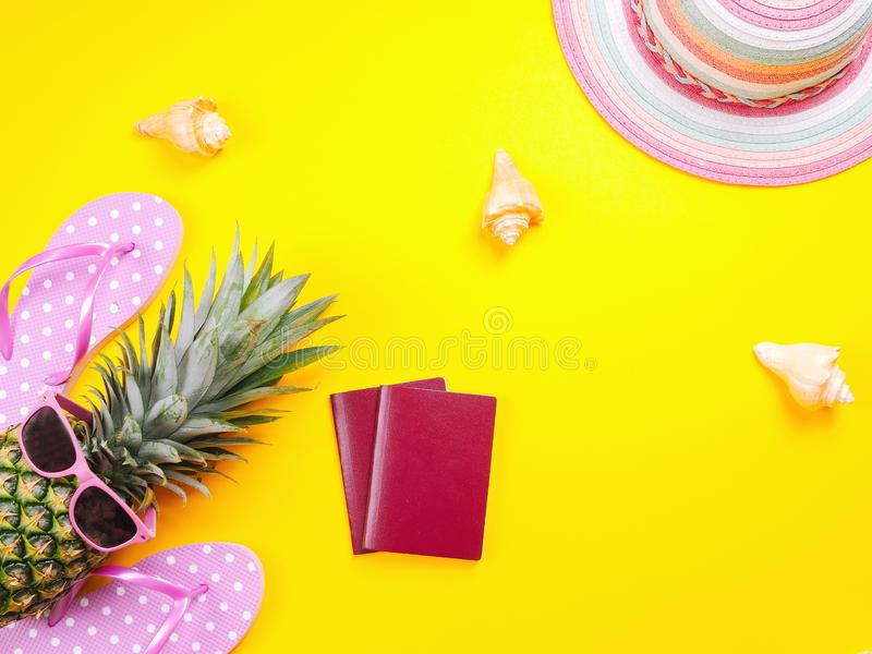 Pineapple wearing sunglasses on a yellow background. Summer flat lay: two passports, fresh pineapple wearing sunglasses, beach slippers and colorful hat on a stock image