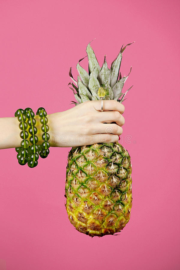 Pineapple in women hands stock photography