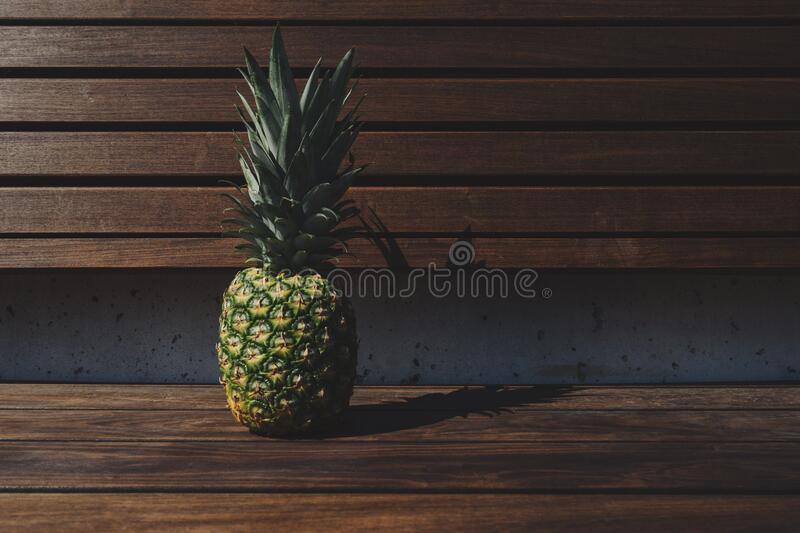 Pineapple on wooden bench royalty free stock photo