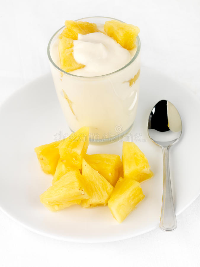 Pineapple yogurt. With pineapple chunks, portrait format, high key image royalty free stock photos
