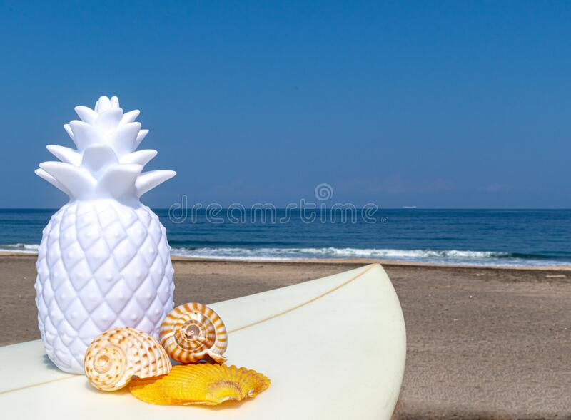 Pineapples on the beach with a blue ocean in the background. Yellow and white royalty free stock images