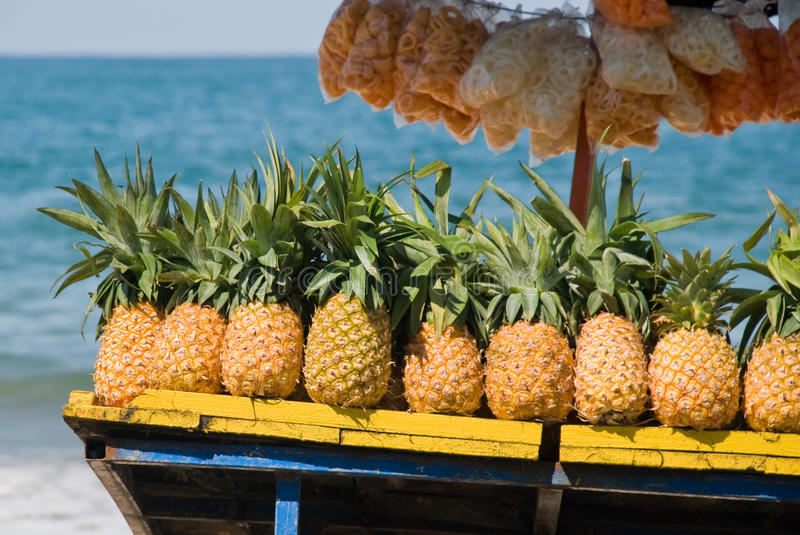 Pineapples for sale on tropical beach. Fresh tropical pineapples and packaged chips for sale on tropical beach in Mexico royalty free stock photos