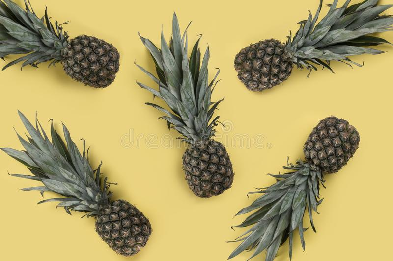 Pineapples on yellow background - Tropical fruits background royalty free stock images