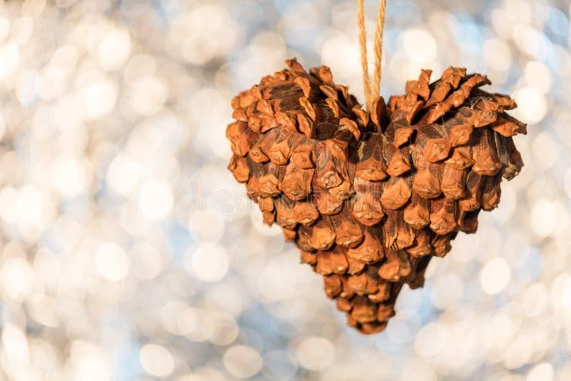 Pinecone在心脏形状的圣诞节装饰在闪耀bo的 库存图片