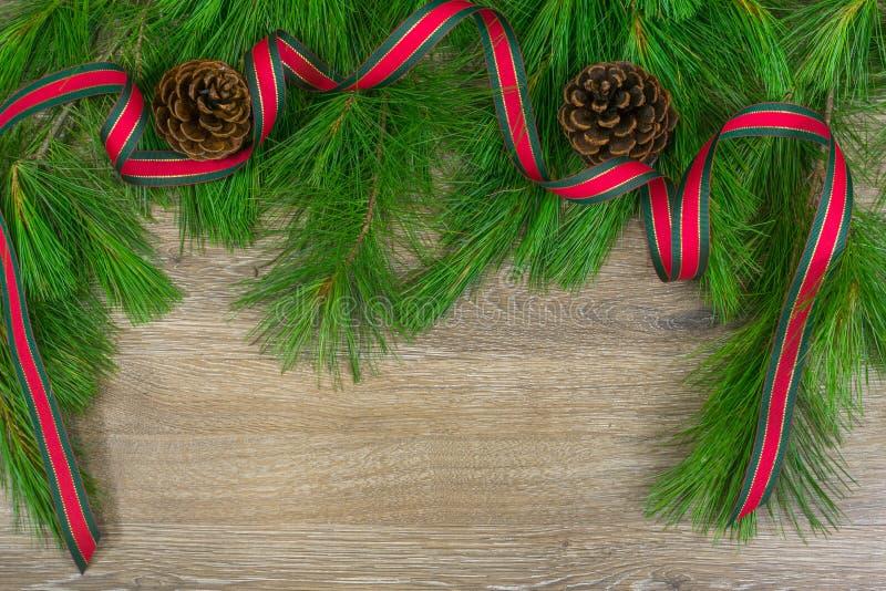 Pinecones junto con cinta roja y verde de la Navidad en el perno blanco foto de archivo