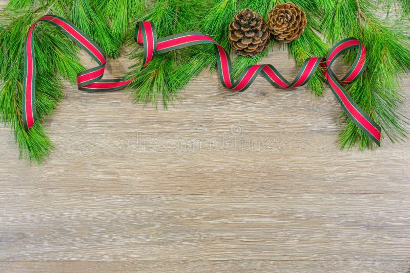 Pinecones junto con cinta roja y verde de la Navidad en el perno blanco imagen de archivo