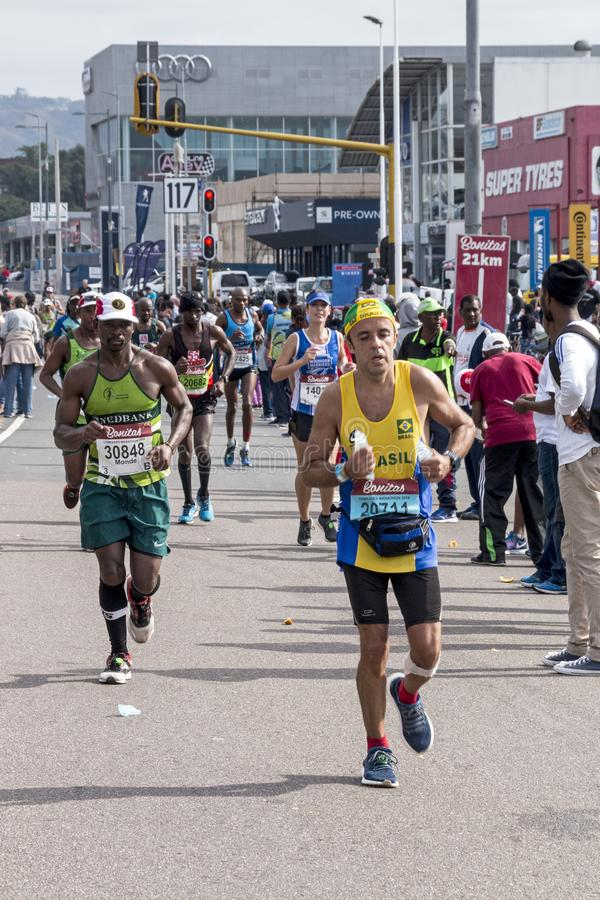 Runners Participating in the Comrades Marathon in South Africa. PINETOWN, DURBAN, SOUTH AFRICA - JUNE 10, 2018: Midday many spectators and unknownn runners royalty free stock image