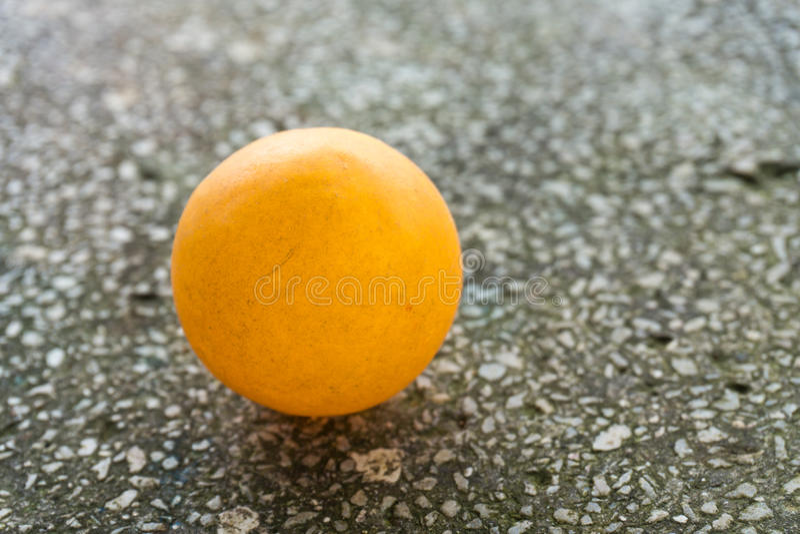 Ping-pong anaranjado en el piso foto de archivo