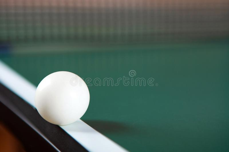 A ping pong ball on the edge of a green ping pong table. Close-up. Ping-pong net royalty free stock photo