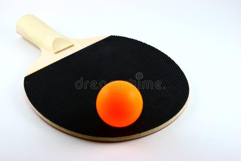Ping-pong orange sur 'bat' noire photos stock