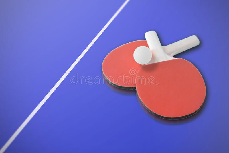 Ping pong paddles and a ball on a blue table. Empty copy space. For Editor`s content stock photo