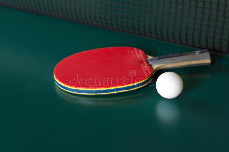 Ping-pong racket and a ball on a green table. ping-pong net royalty free stock image