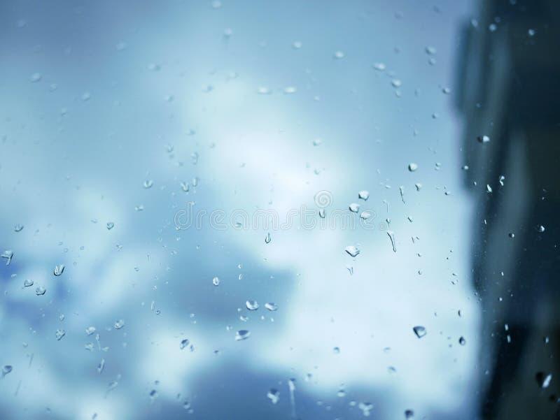 Pingos de chuva em uma placa de janela durante uma tempestade da chuva com as nuvens de tempestade cinzentas azuis no fundo fotografia de stock