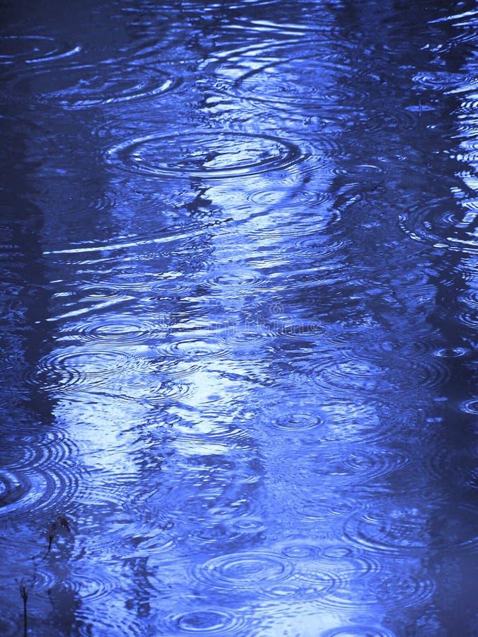 Pingos de chuva na água imagem de stock royalty free