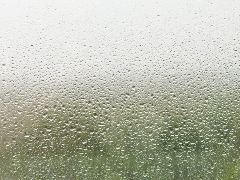 Pingos de chuva na placa de janela home fotografia de stock