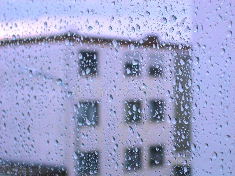 Pingos de chuva no indicador de vidro com opinião do edifício fotos de stock royalty free