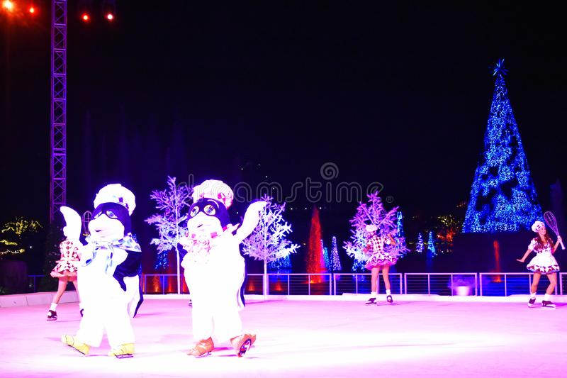 Pinguïnen en de meisjes die op ijs bij Kerstmis de schaatsen tonen op Internationaal Aandrijvingsgebied royalty-vrije stock fotografie