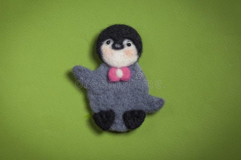 Pinguim do brinquedo feito das lãs em um fundo verde imagem de stock