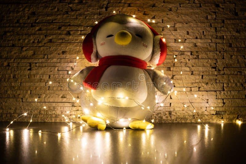 Pinguinspielzeug umgeben durch Girlande mit verziertem Wandhintergrund Foto in der Dunkelheit stockbild