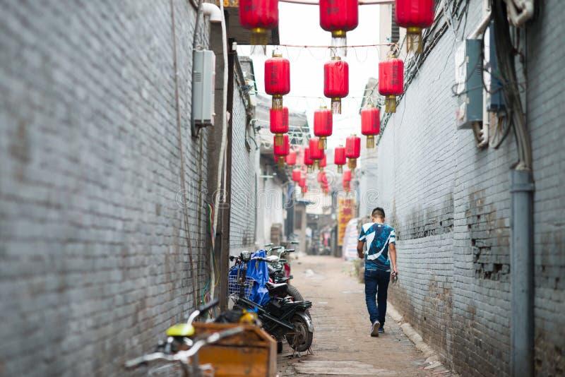 Pingyao, China - 08 14 2016: Un hombre chino que camina en una calle con las linternas rojas en Pingyao La ciudad antigua de Ping fotos de archivo libres de regalías