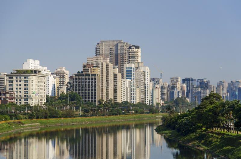 Pinheiros flod och byggnader fotografering för bildbyråer