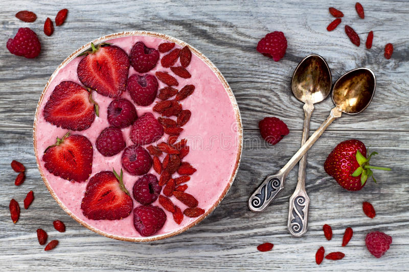 Pink acai, maca powder smoothie bowl topped with sliced strawberries, raspberries and goji berries. royalty free stock image